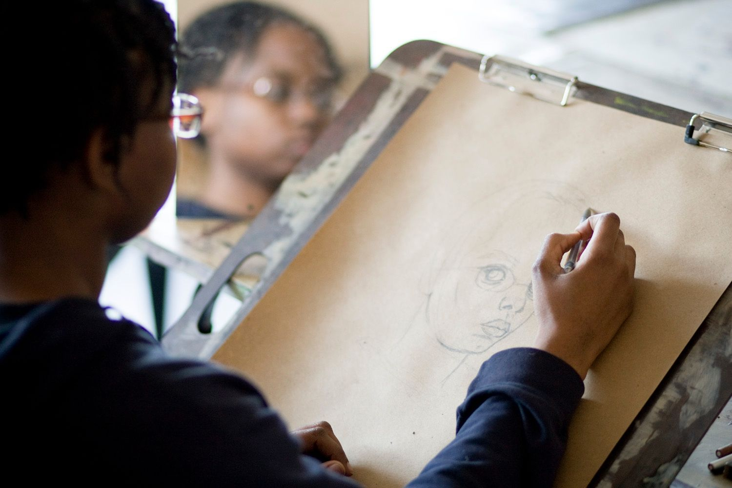 A picture of a BAA student from over the shoulder while they look in a mirror and start a self-portrait.