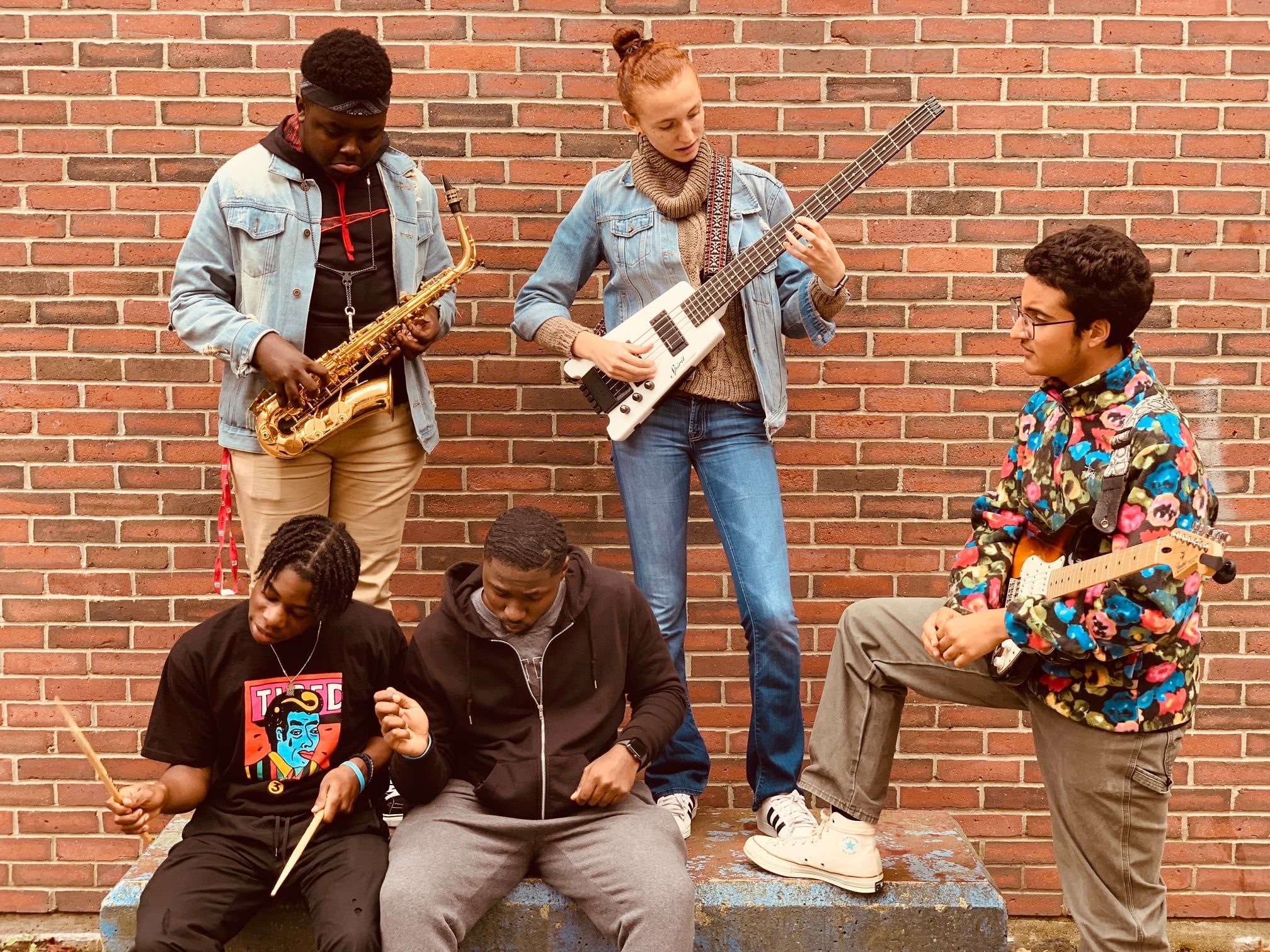 A picture of BAA students holding instruments against a brick wall.