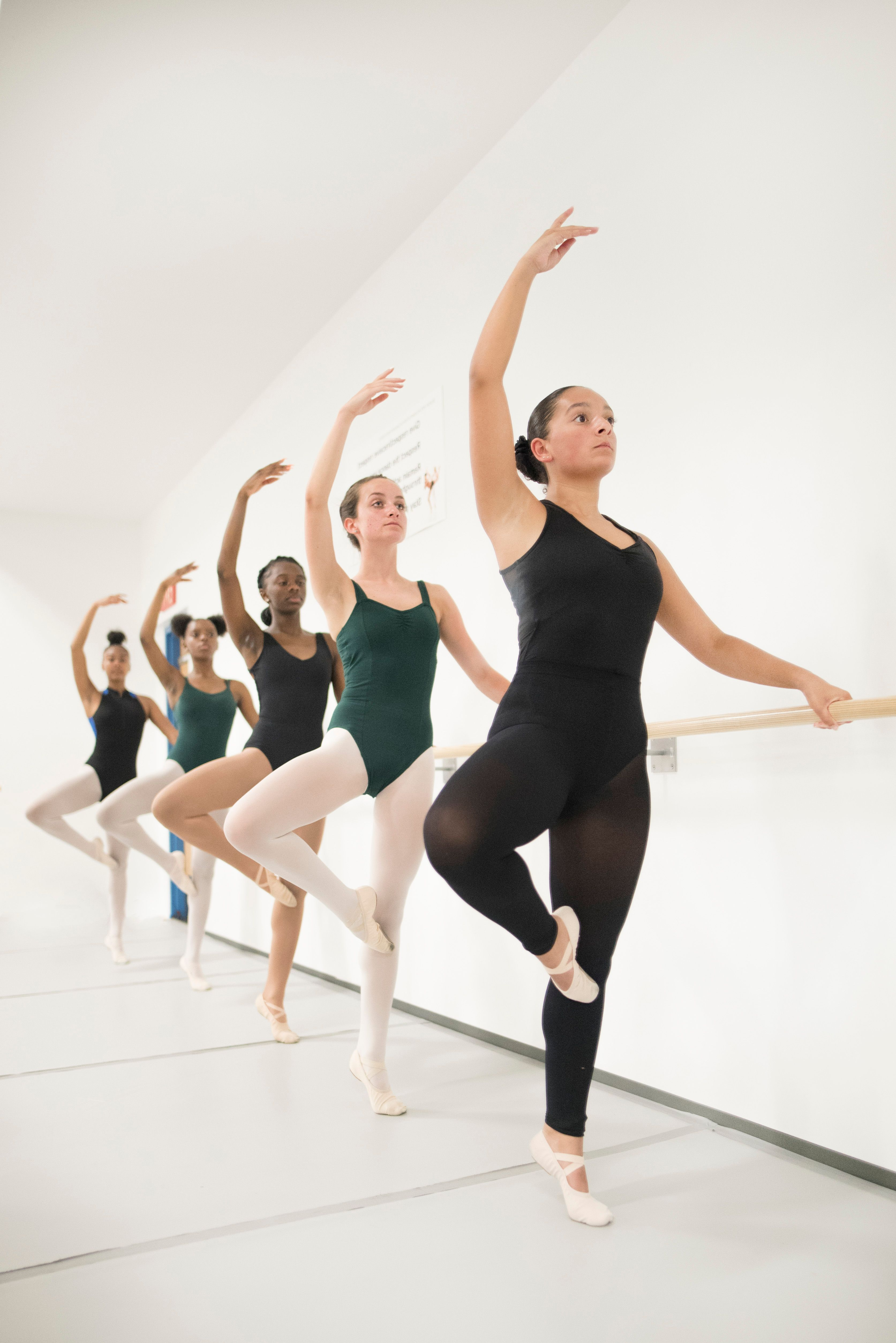 A picture of 5 BAA dance majors all in the same pose with an arm gracefully arched over their head while working on a ballet barre.