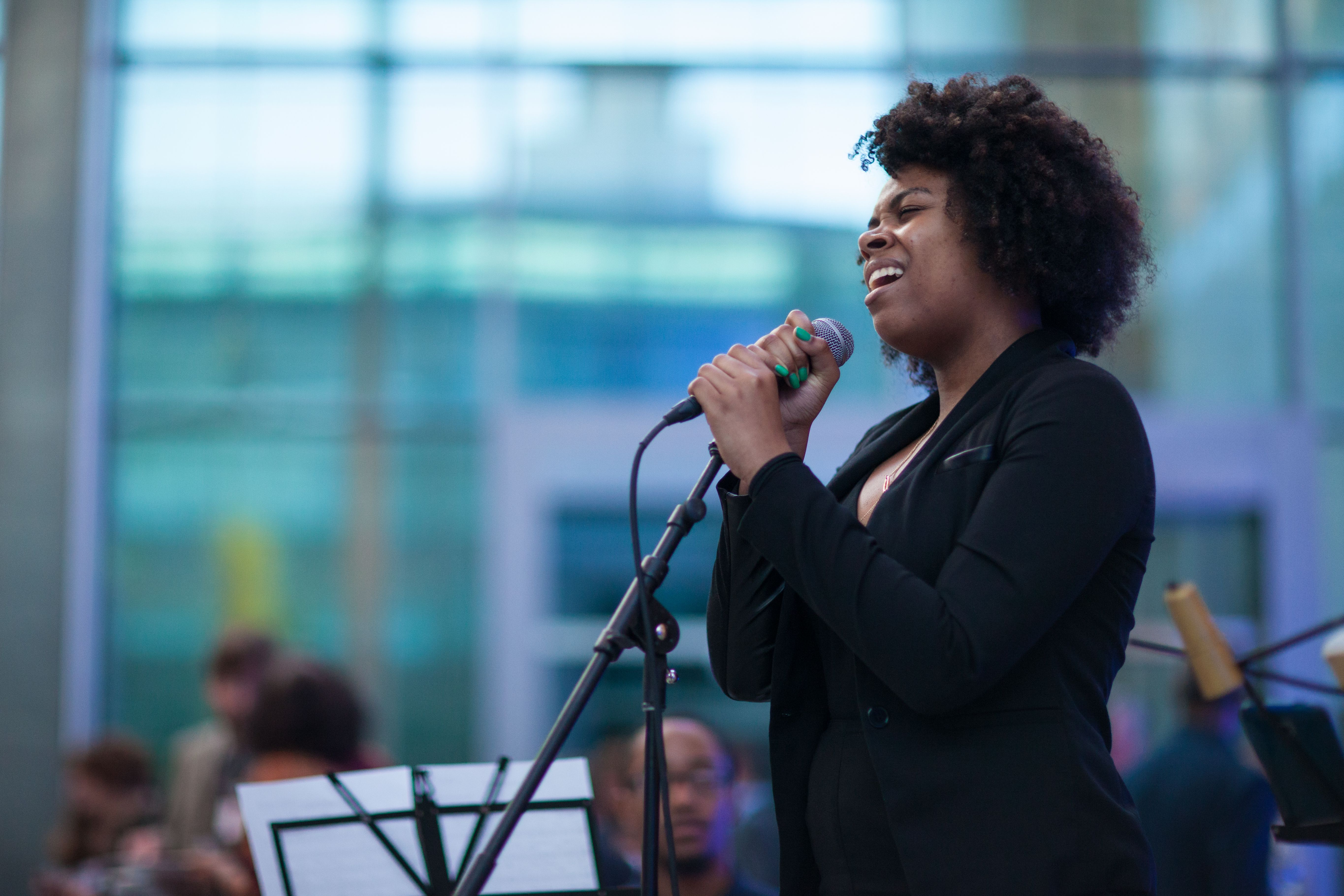 A picture of a BAA vocalist singing while gripping a microphone with a band in the background.