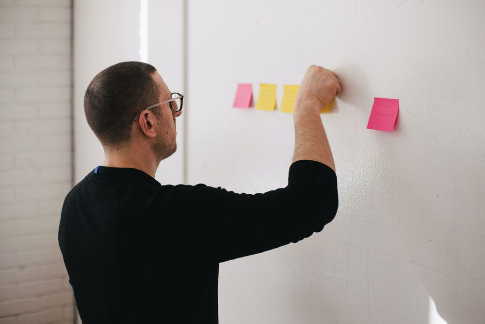 A man with glasses putting a post it on the wall
