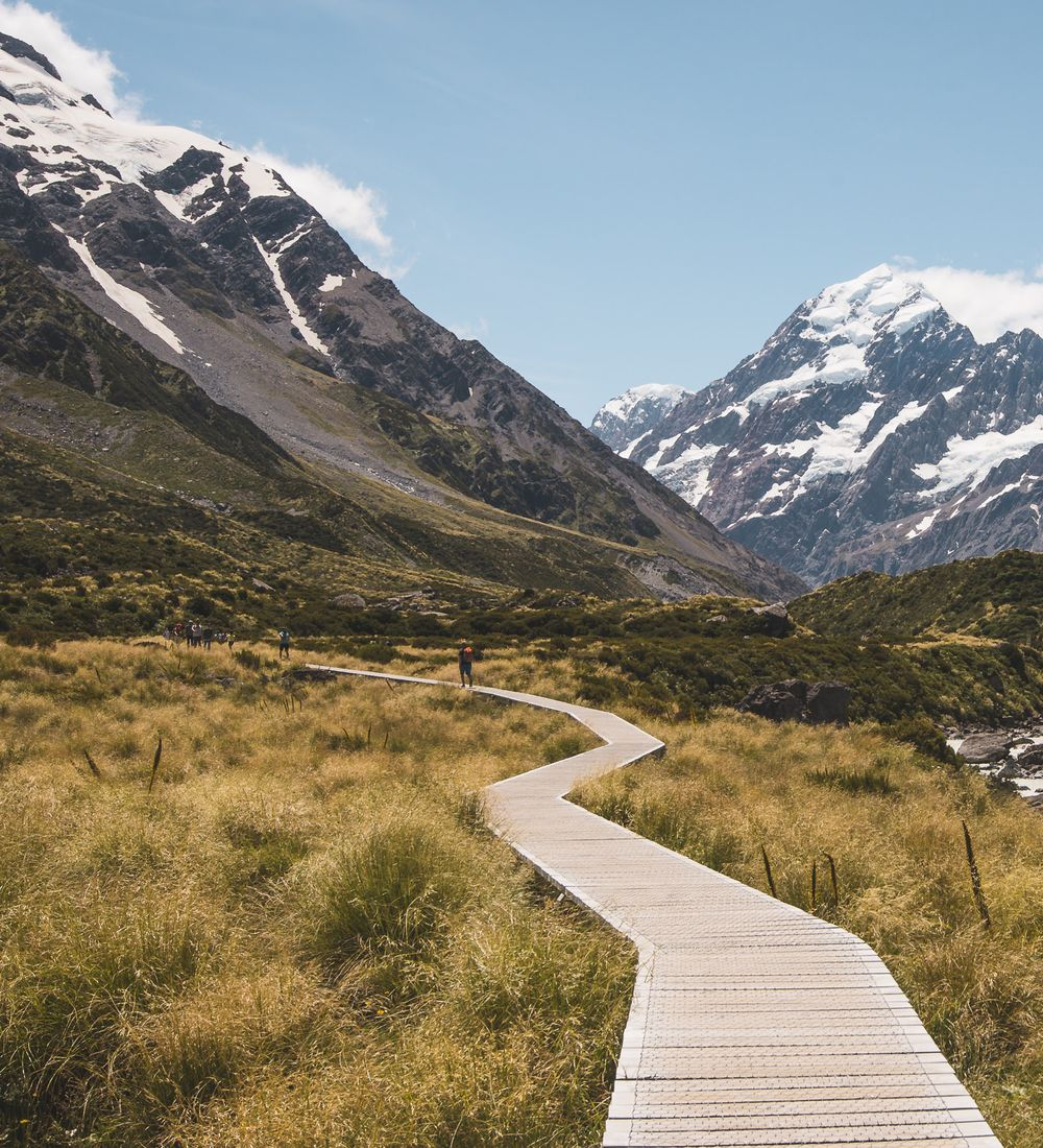 a person walking along a boardwalk with mountains in the distance in new zealand