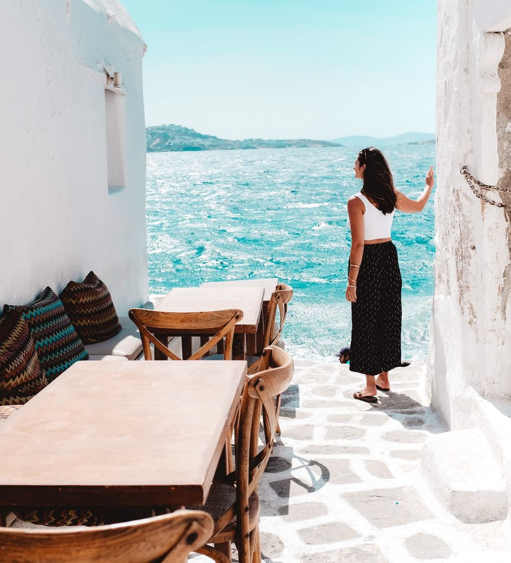 a woman looking out to sea in mykonos greece