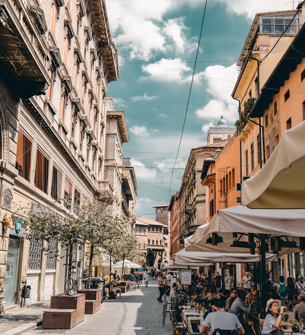 street scene in bologna with diners eating at outdoor restaurants