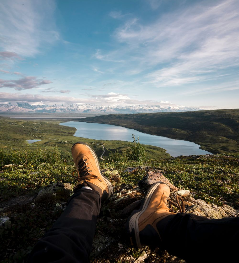 hiking shoes of a traveler sitting on a hill overlooking a lake in denali national park