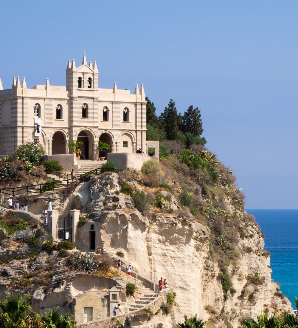 people climbing stairs up to santa maria monastery in tropea italy