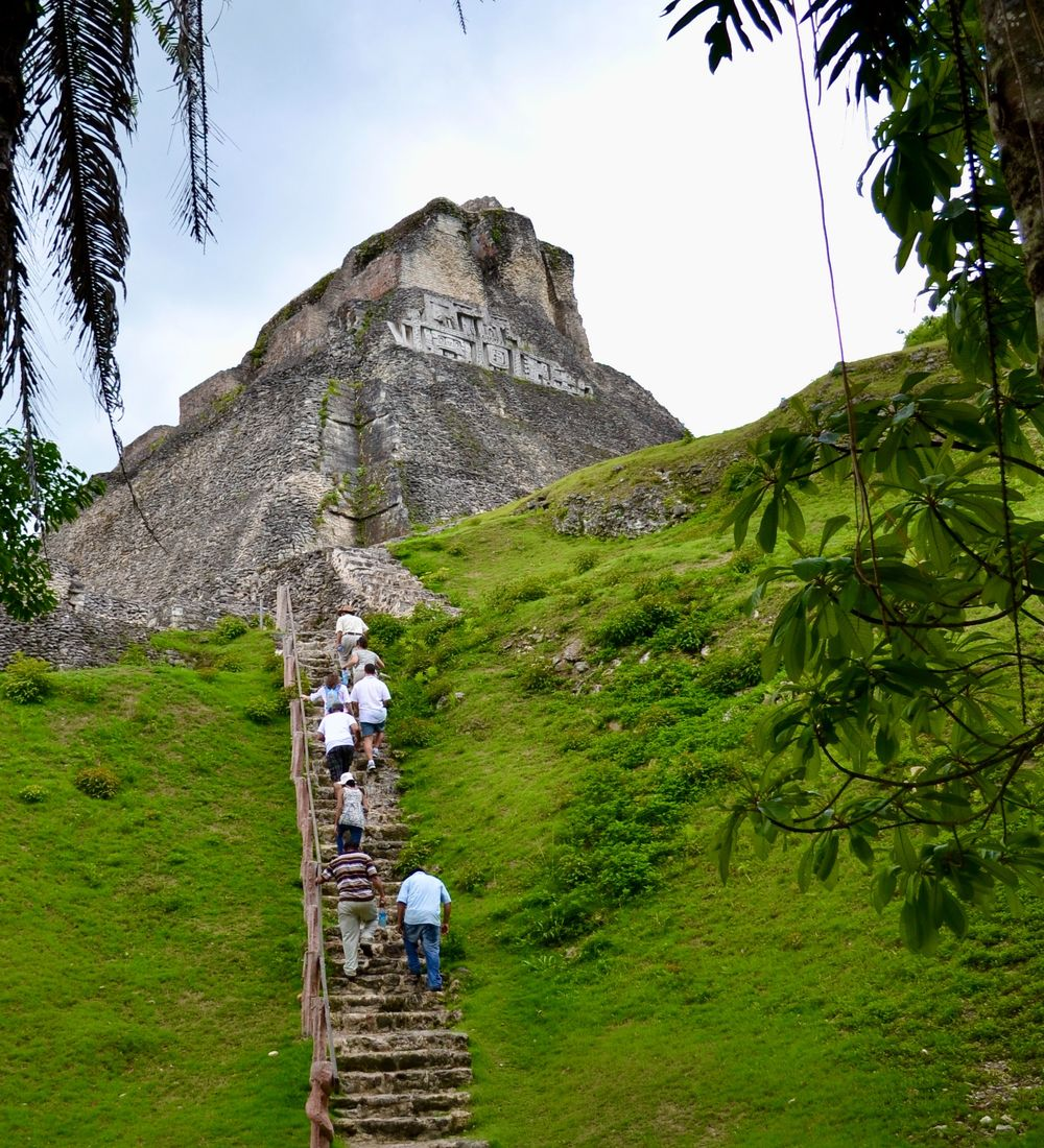 several travelers climbing the xunantunich mayan ruins