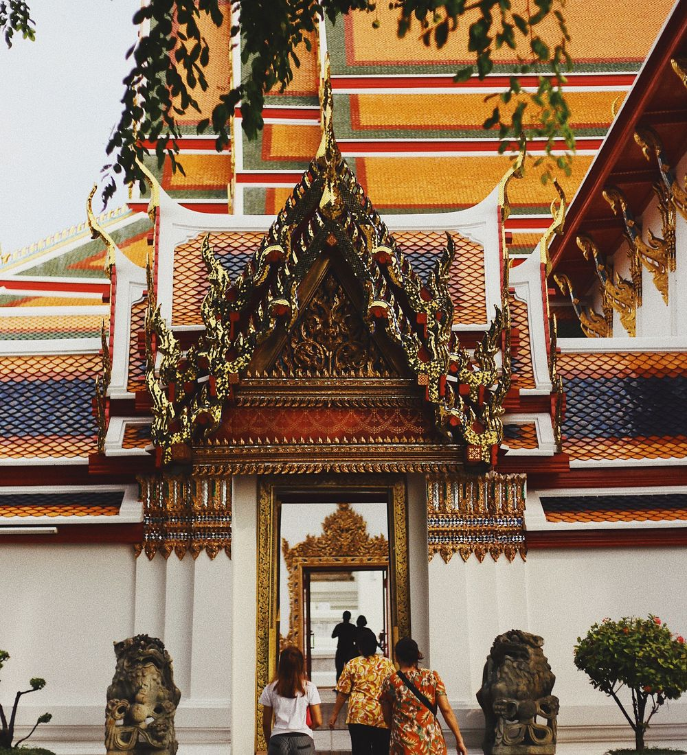 three people stepping into the entrance of wat pho temple in bangkok thailand