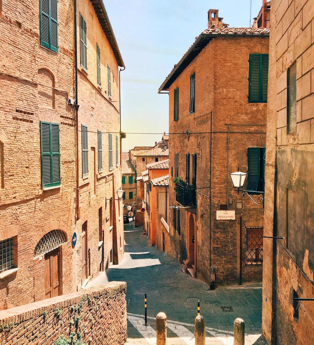 brick buildings on a small street in siena italy