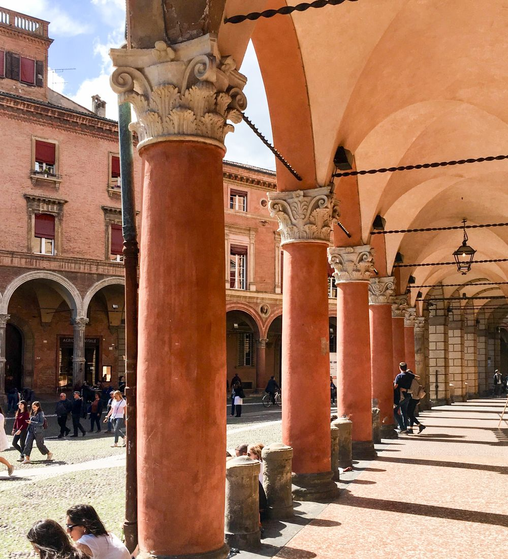 people walking outside a building with columns in bologna italy