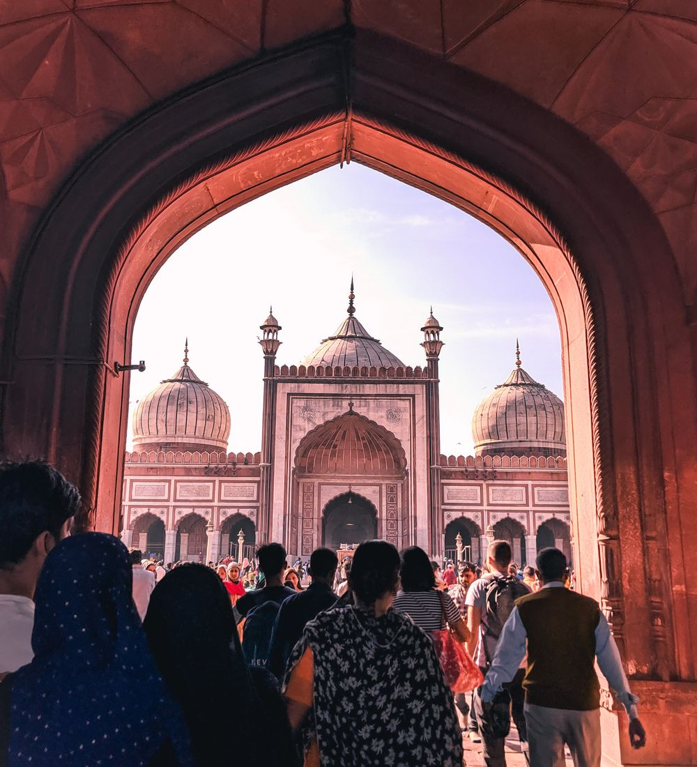 people walking through the arch to the domed mosque of jama masjid in old delhi