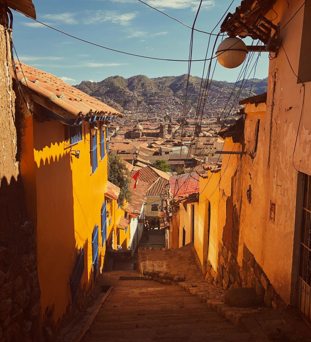 yellow houses on a cobblestone street in cuzco peru