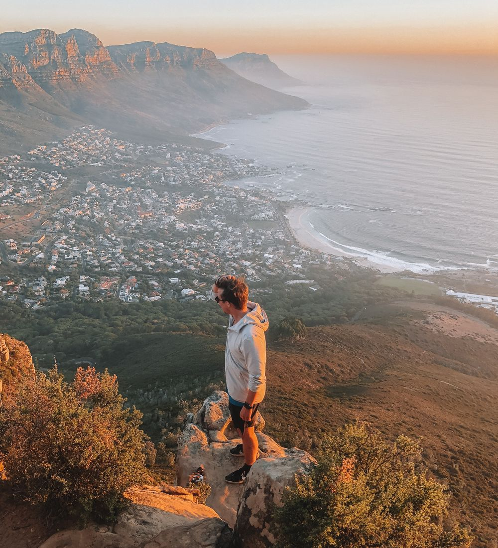 a man standing on a cliff overlooking the coast of cape town south africa