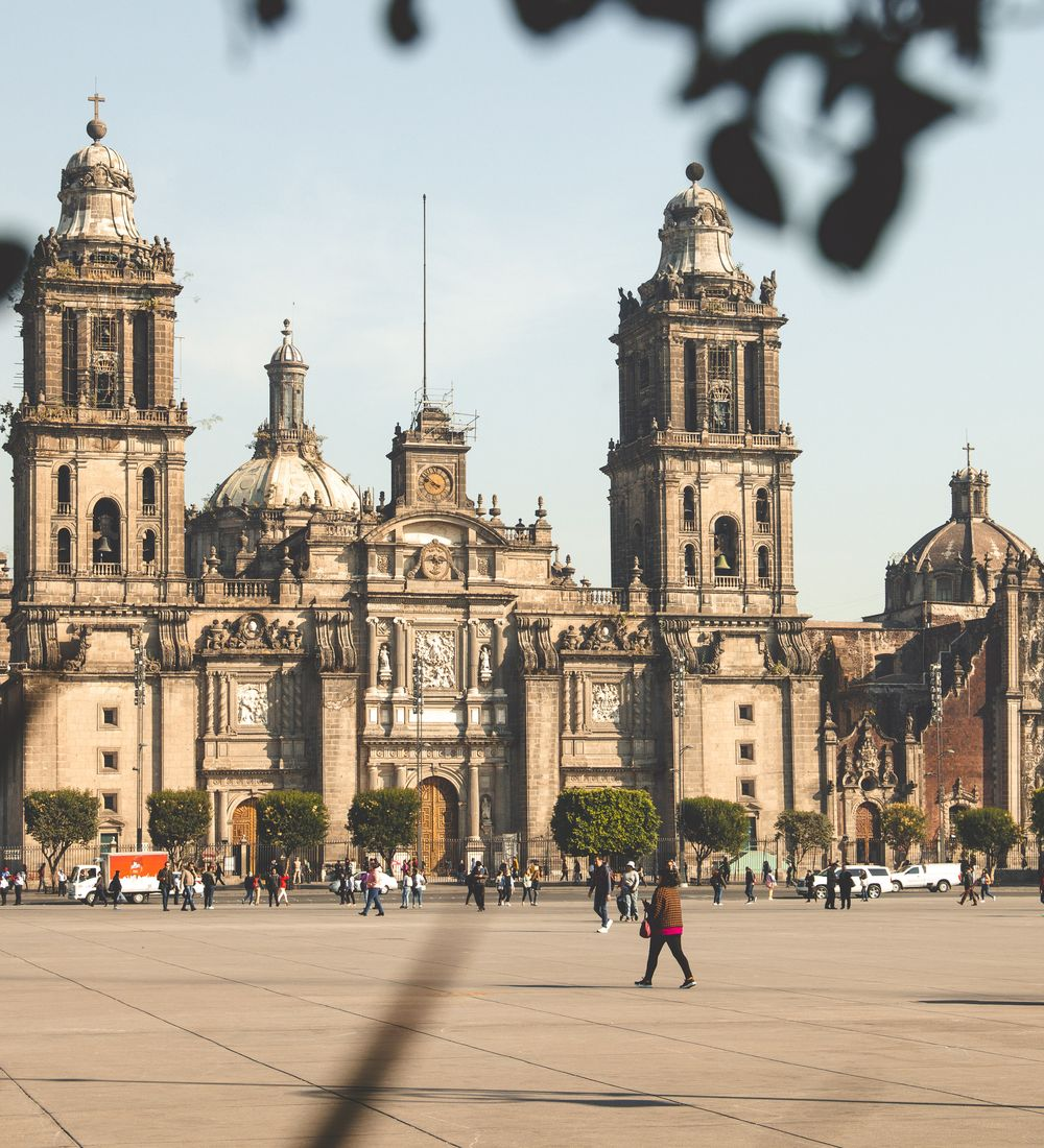 travelers walking in front of the metropolitan cathedral in mexico city