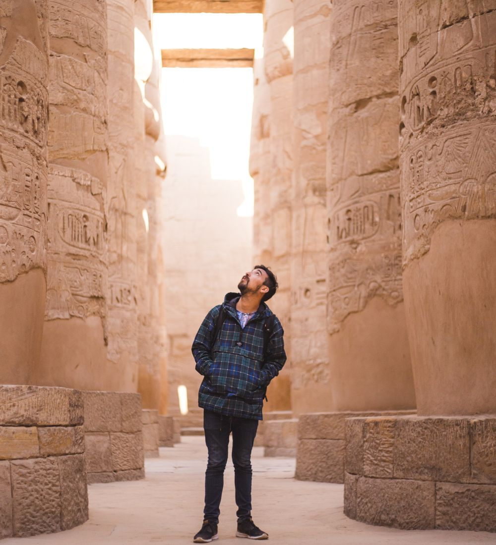 a man standing and looking up at columns surrounding him at the temple of karnak