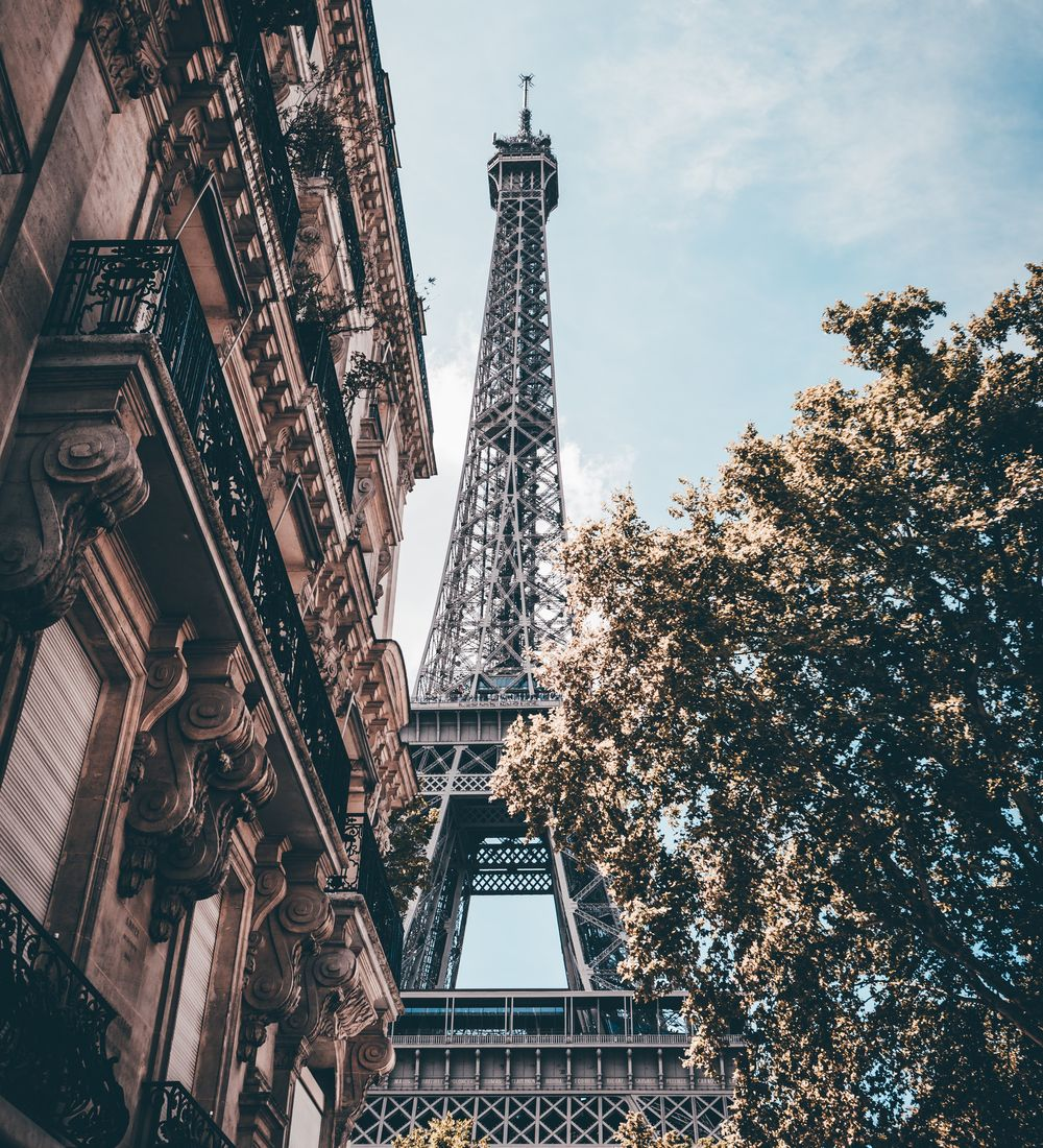 looking up at the eiffel tower from street level on a sunny day