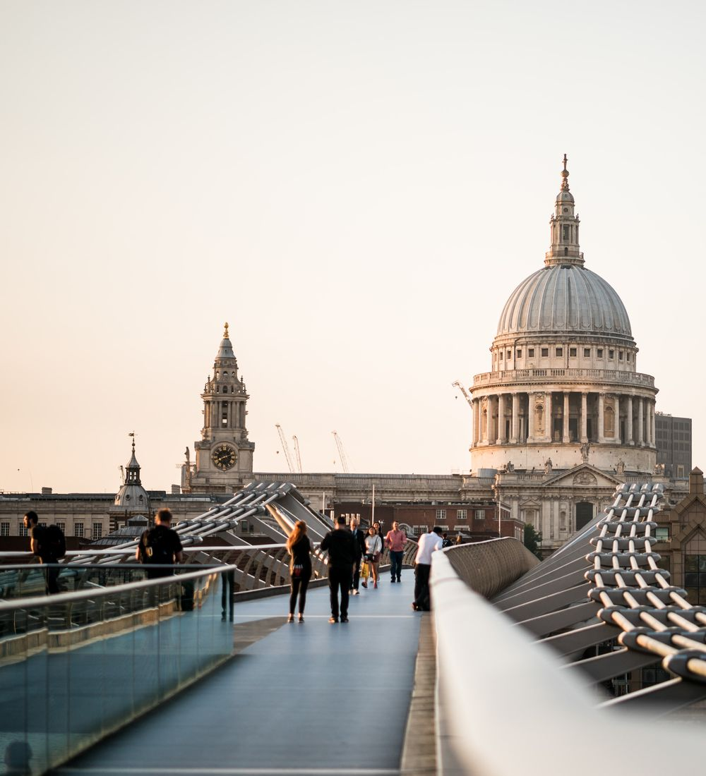 people walking along the millenium bridge in london england