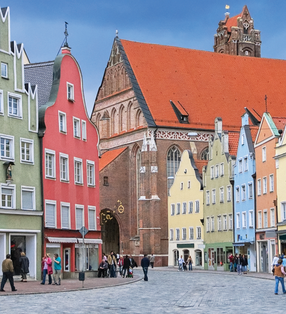 people walking around square with colorful buildings in germany