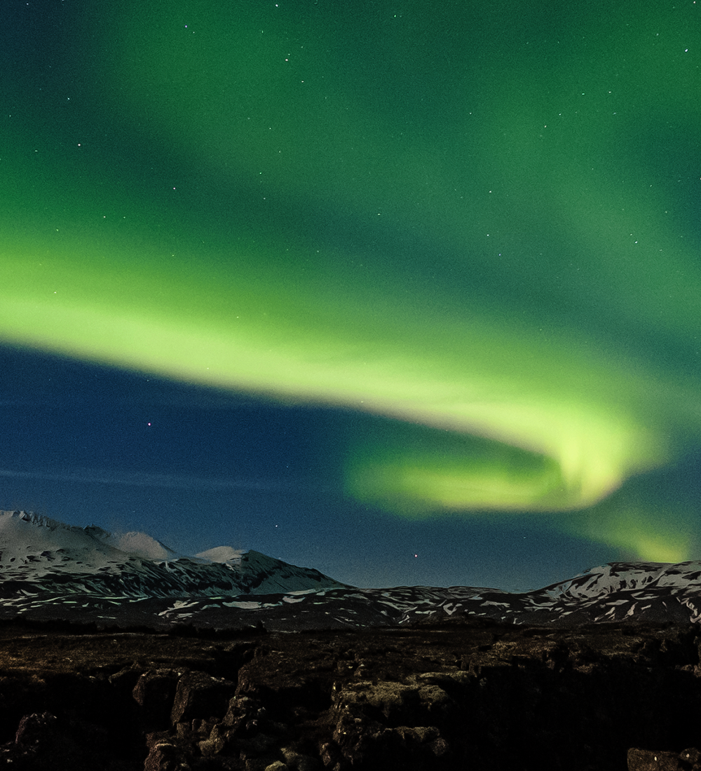 green northern lights floating above mountains in iceland