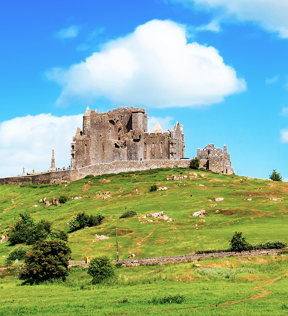 castle on top of a green grass hill in ireland on sunny day