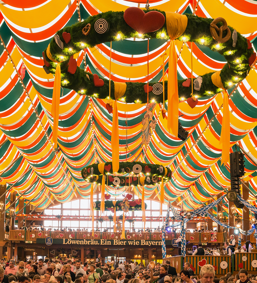 green yellow and red german beer tent filled with people at oktoberfest