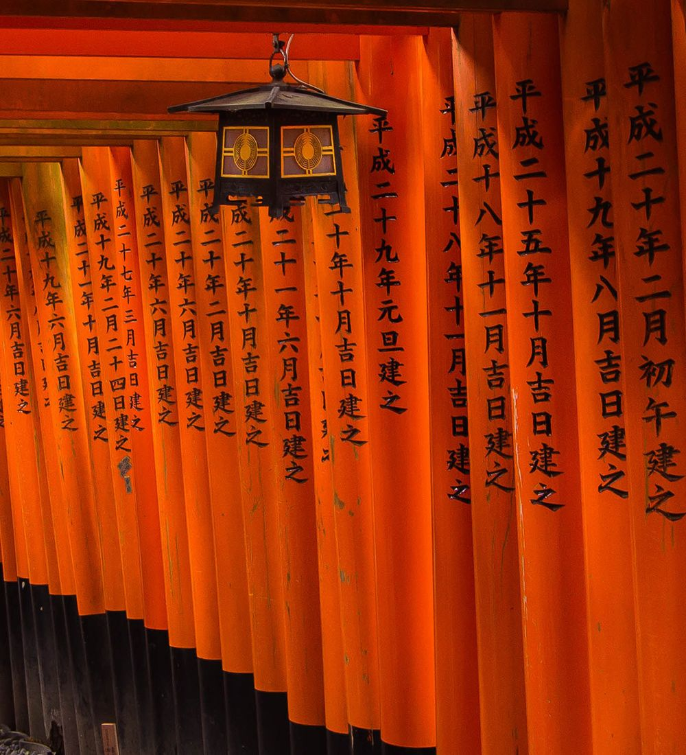 red torii gates and lamp along a path at fushimi inari taisha