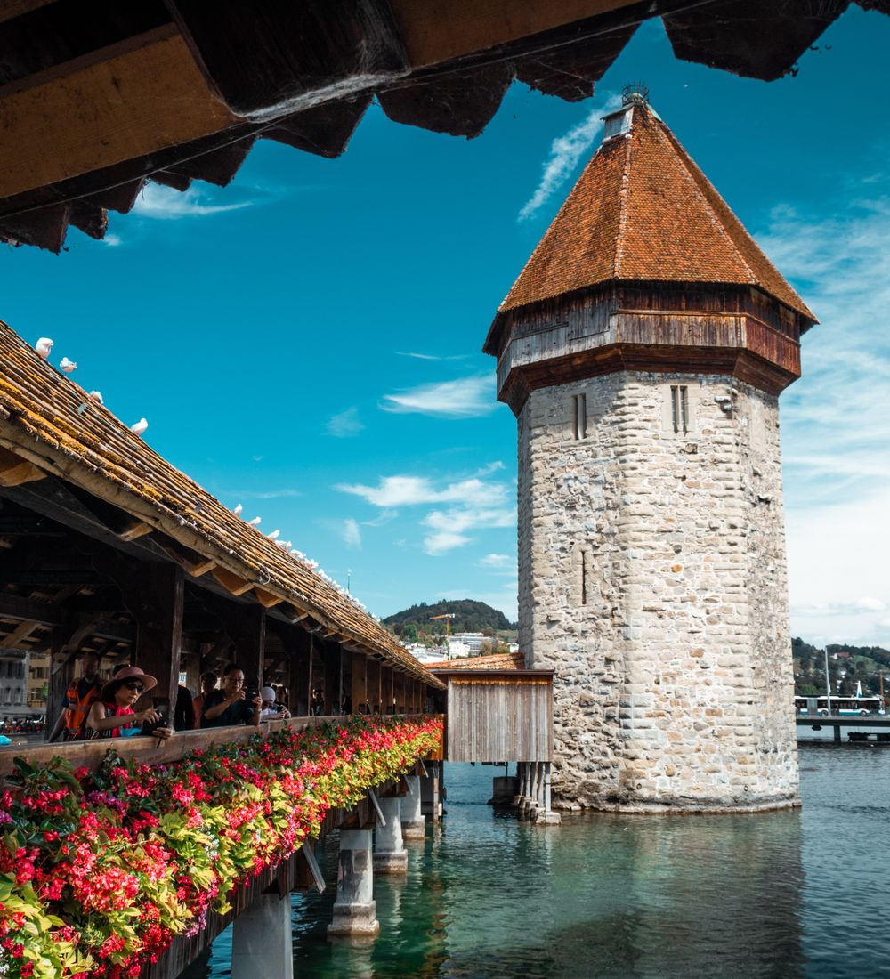 people standing on the flower lined chapel bridge in lucerne switzerland