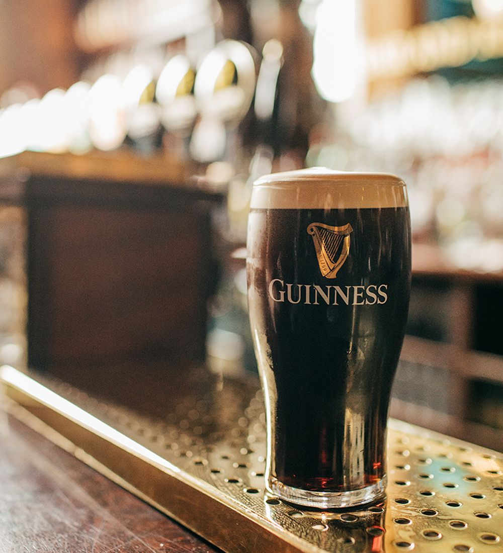 A tall glass of Guinness in an Irish pub