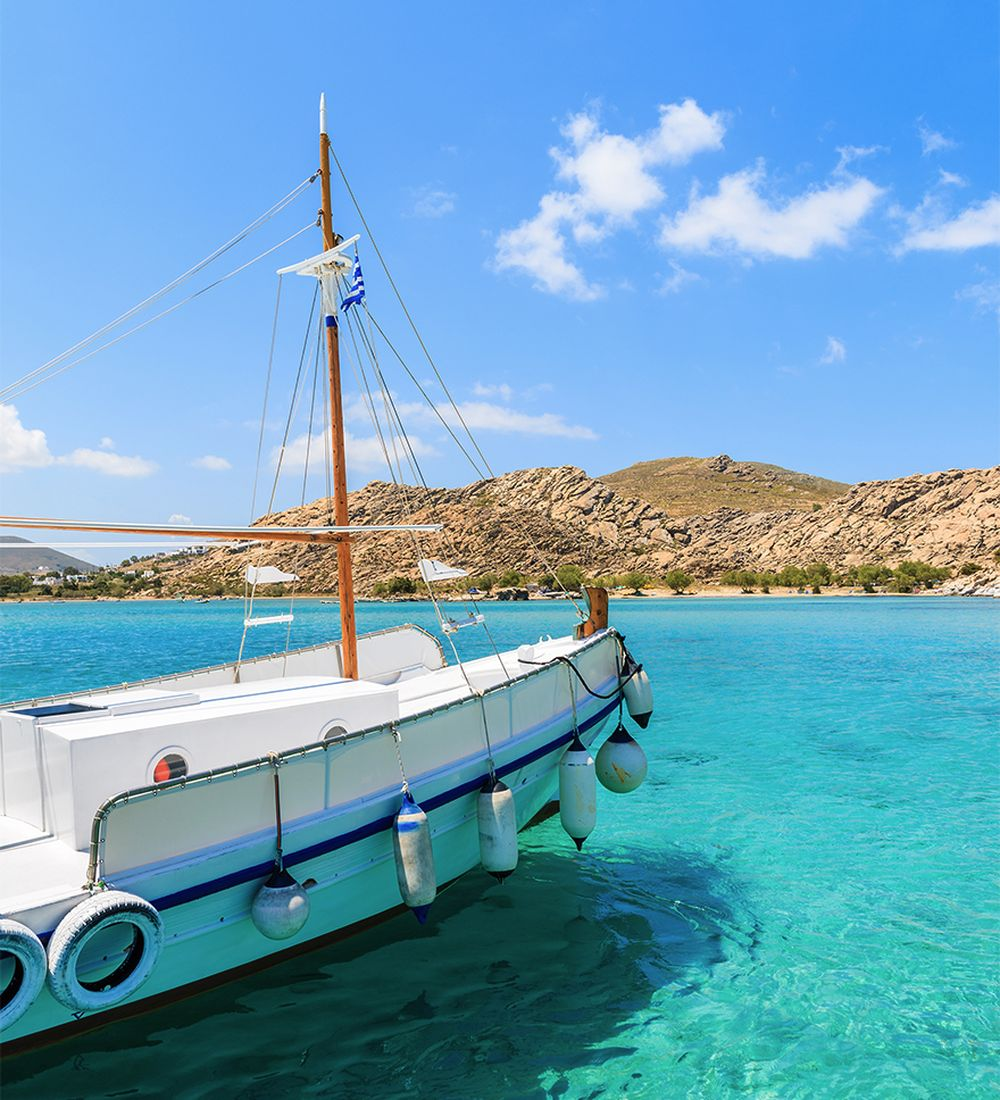 Bow of Greek fishing boat sailing on turquoise sea water on Paros island Greece