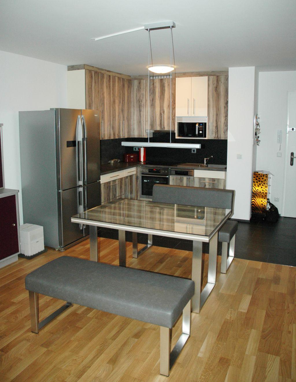 L-Küche mit freistehendem Kühlschrank und Esstisch mit Sitzbank