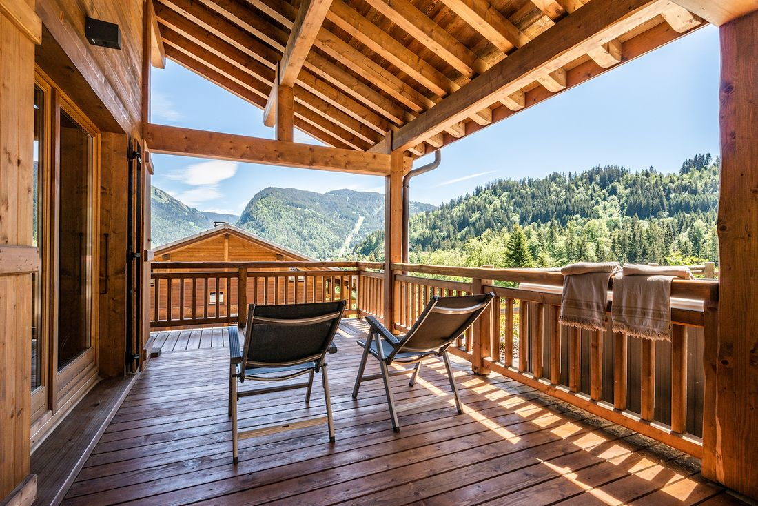 Large covered wooden terrace with two sun beds at Balata luxury chalet in Morzine