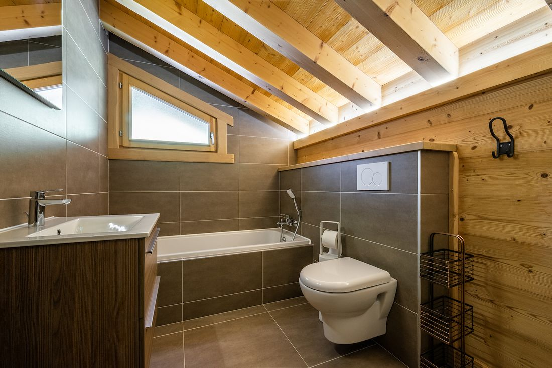 Modern bathroom with bathtub and toilet at Balata luxury chalet in Morzine