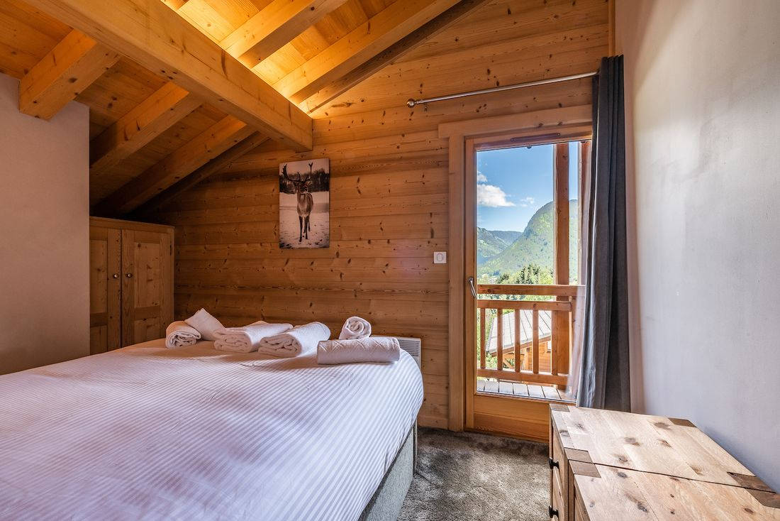 Ensuite bedroom with balcony overlooking the French Alps at Balata luxury chalet in Morzine