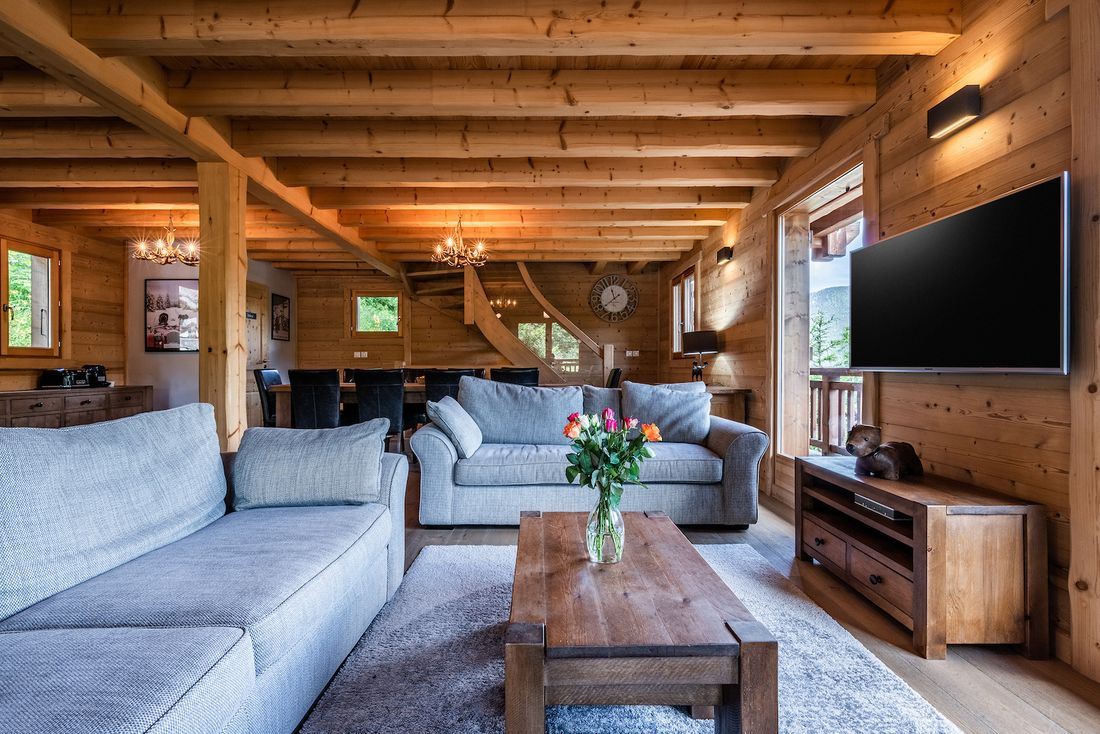 Modern living room with two light grey sofas and a TV at Balata luxury chalet in Morzine
