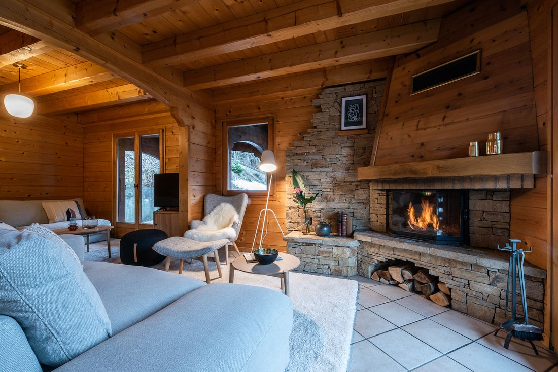 Light grey sofas and stoned fireplace at Doux Abri chalet in Morzine