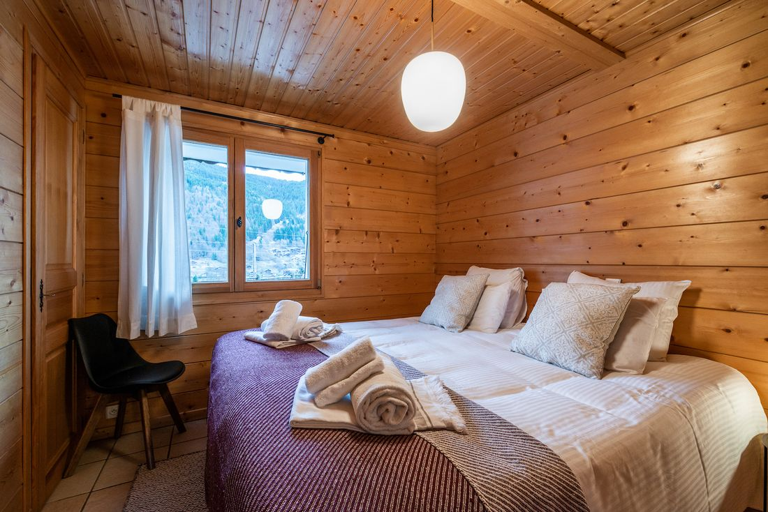 Wooden double bedroom with fresh towels at Doux Abri chalet in Morzine