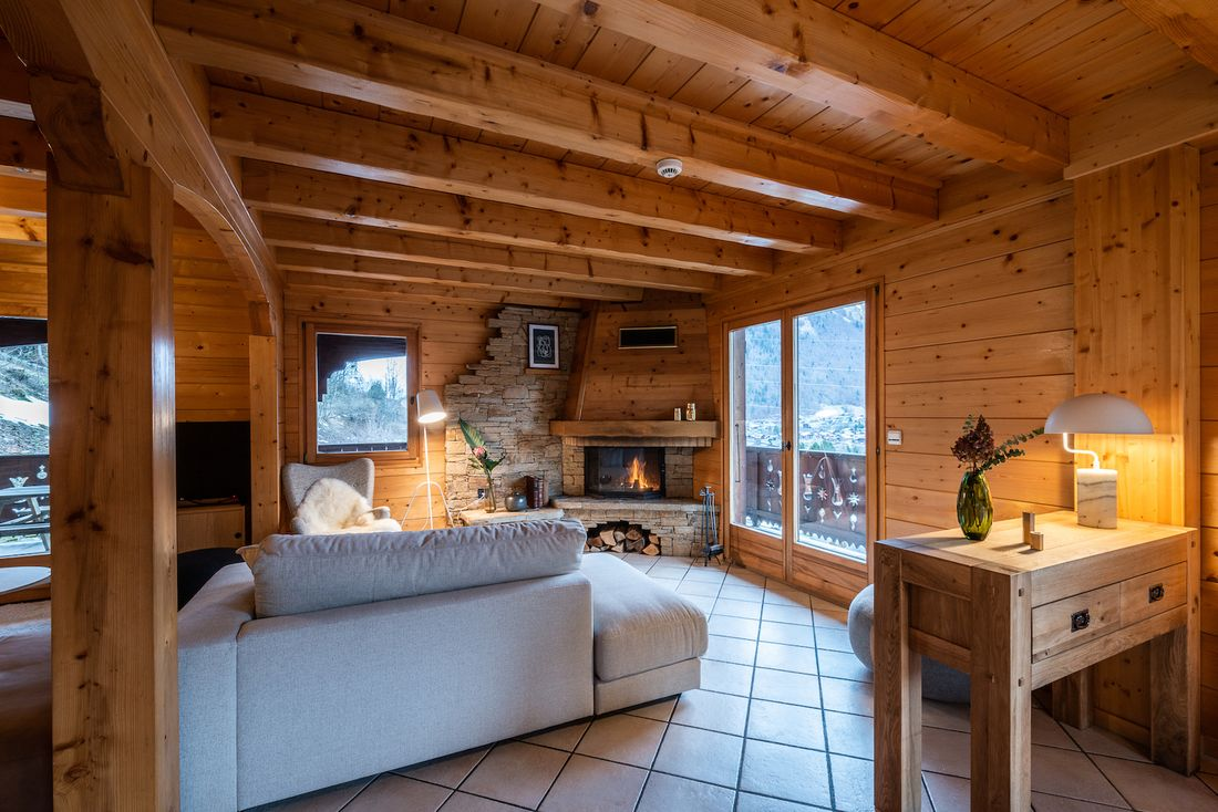 Cosy living room with stoned fireplace at Doux Abri chalet in Morzine