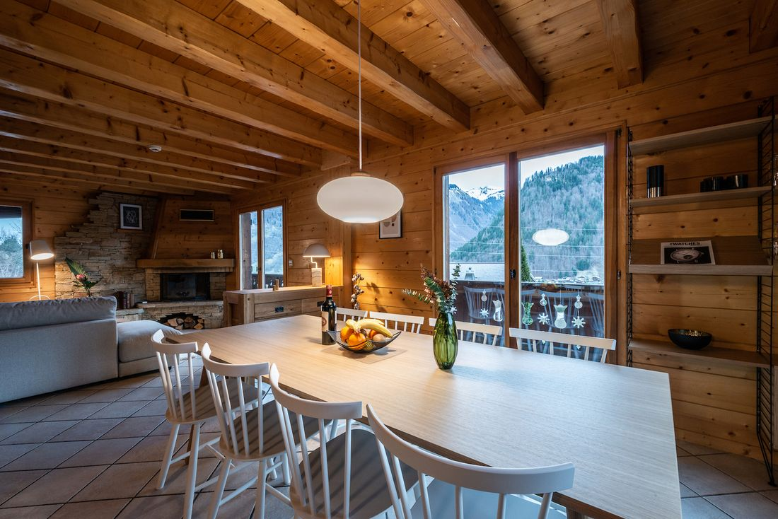 Open dining room and living room with mountain views at Doux Abri chalet in Morzine