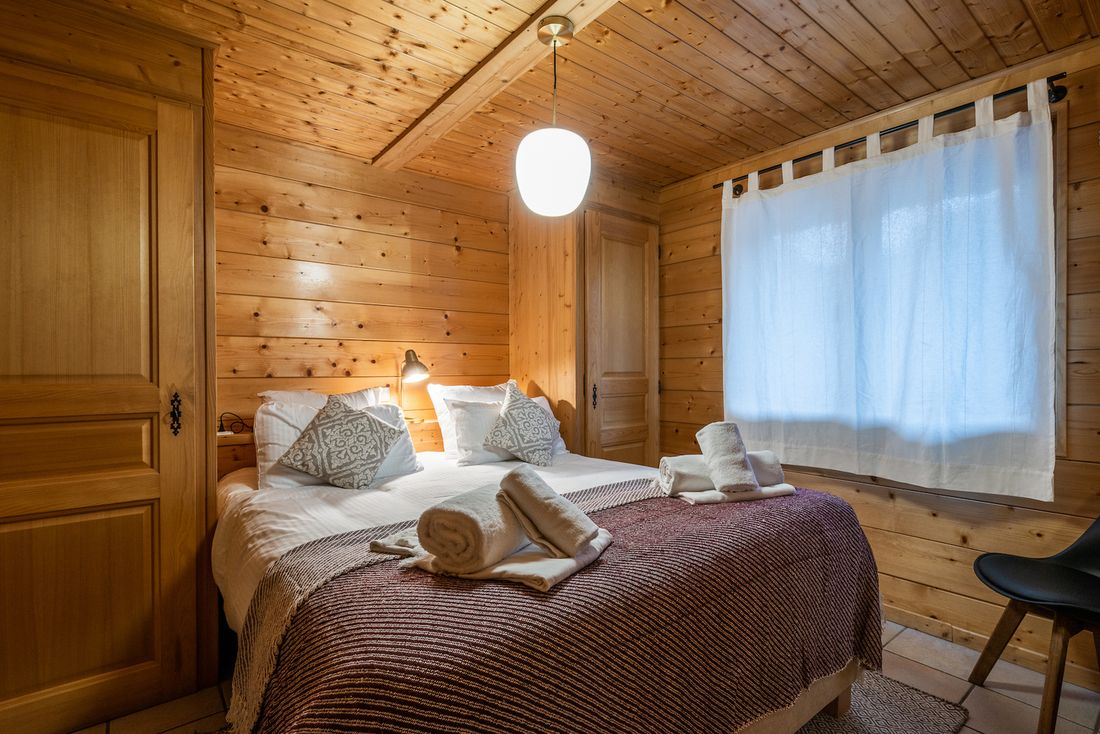 Wooden double bedroom at Doux Abri chalet in Morzine