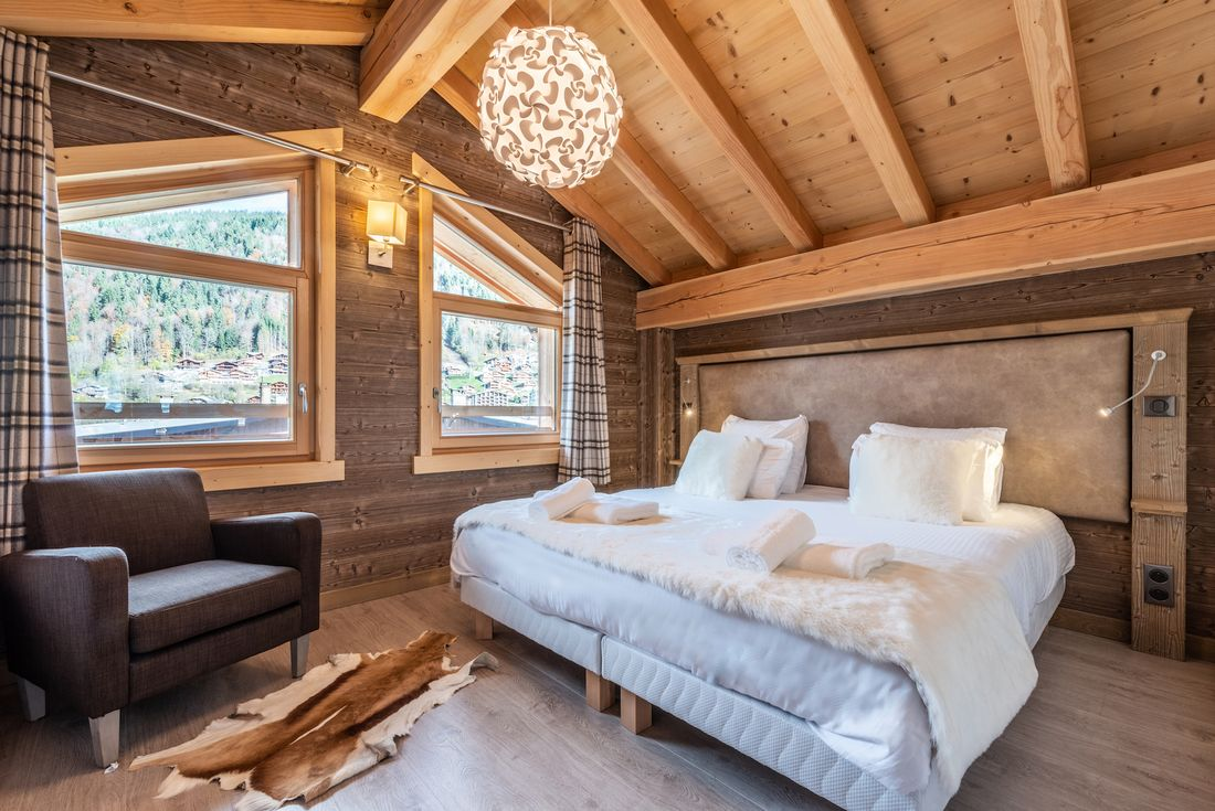 Cosy double bedroom with tartan curtains and faux-fur details at Etoile accommodation in Morzine