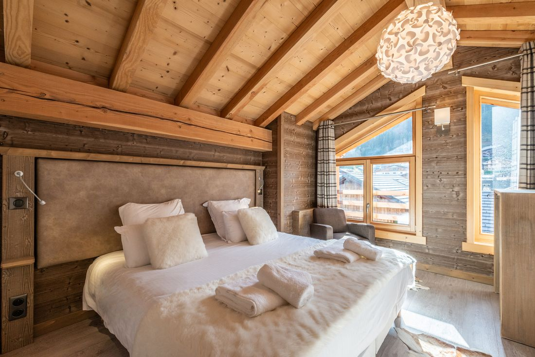 Cosy double bedroom with white faux-fur details at Etoile accommodation in Morzine
