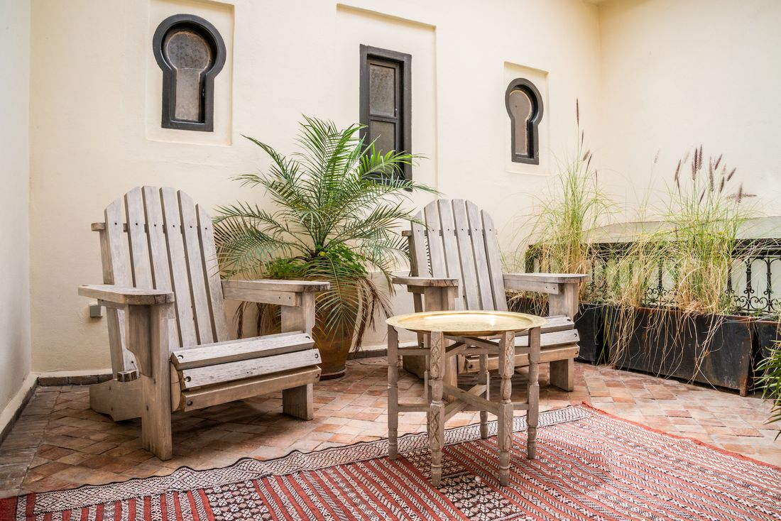 Indoor patio with wooden chairs and berber rug at Adilah riad in Marrakech