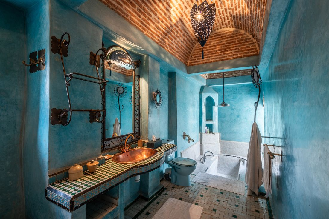 Turquoise blue bathroom with copper sink and moroccan tiles bathtub at Adilah riad in Marrakech
