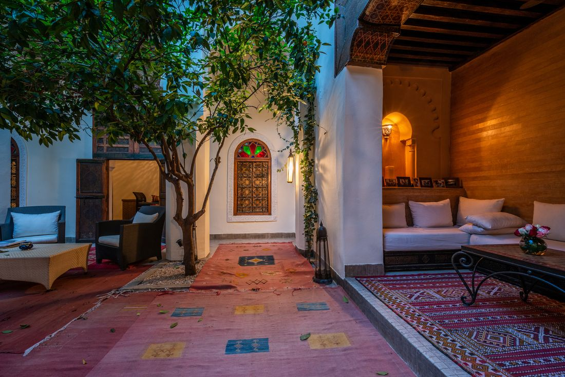 Patio with red berber rugs and lemon tree at Adilah riad in Marrakech
