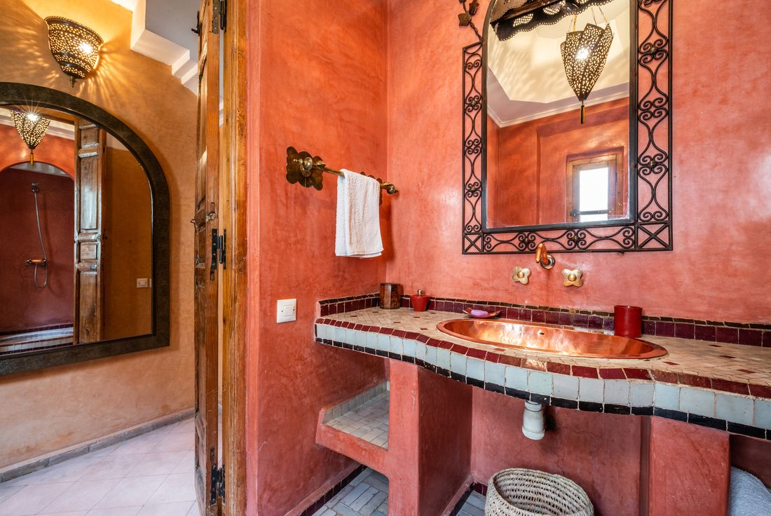 Terracotta-coloured walls in the bathroom of Adilah riad in Marrakech