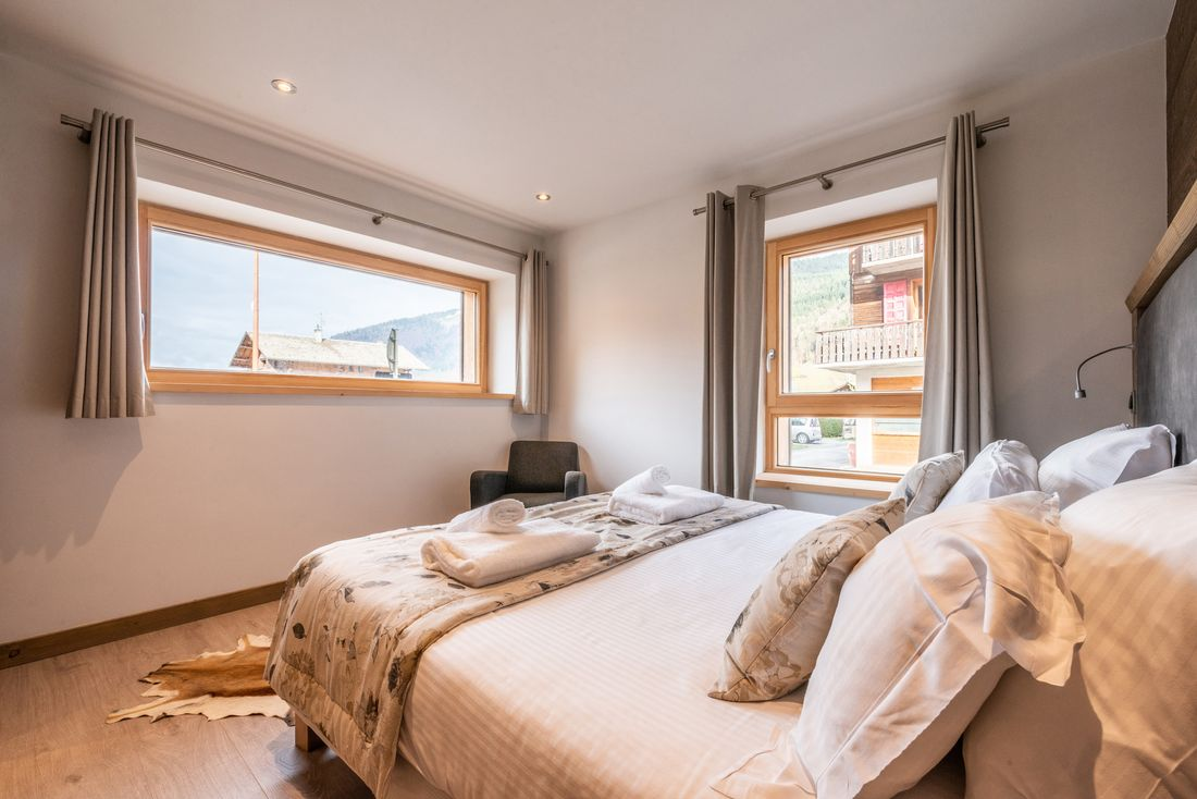 Bright double bedroom with views over the town at Ourson accommodation in Morzine