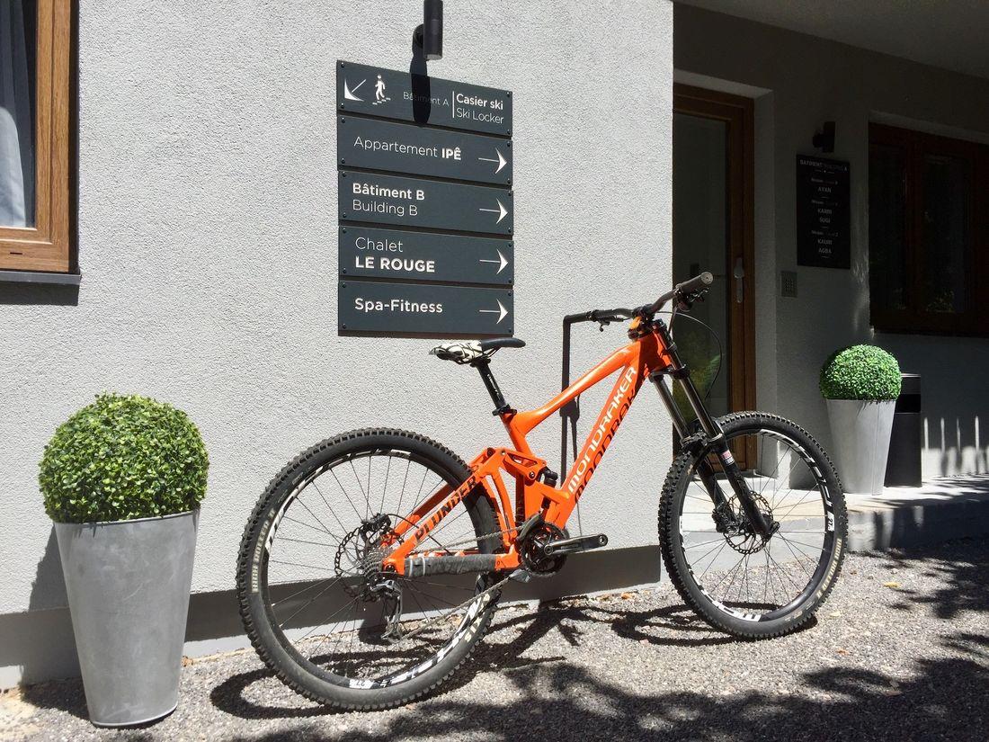 Orange mountain bike in front of Iroko accommodation in Morzine