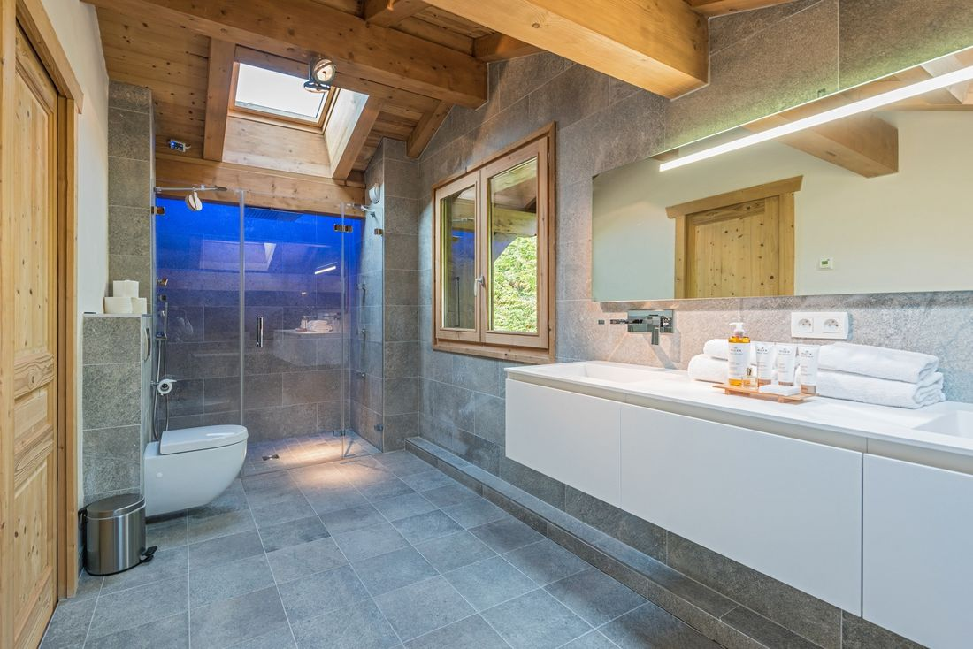Stone bathroom with shower and roof window at Omaroo II luxury chalet in Morzine