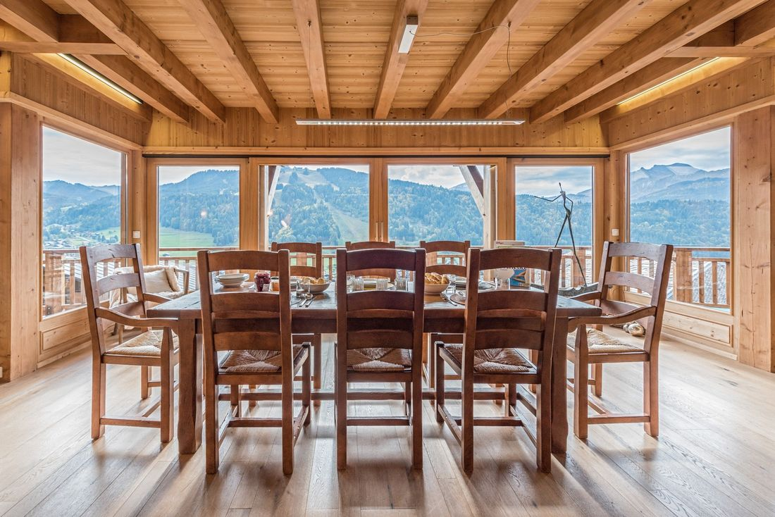Large wooden dining table with views over the Alps at Omaroo II luxury chalet in Morzine