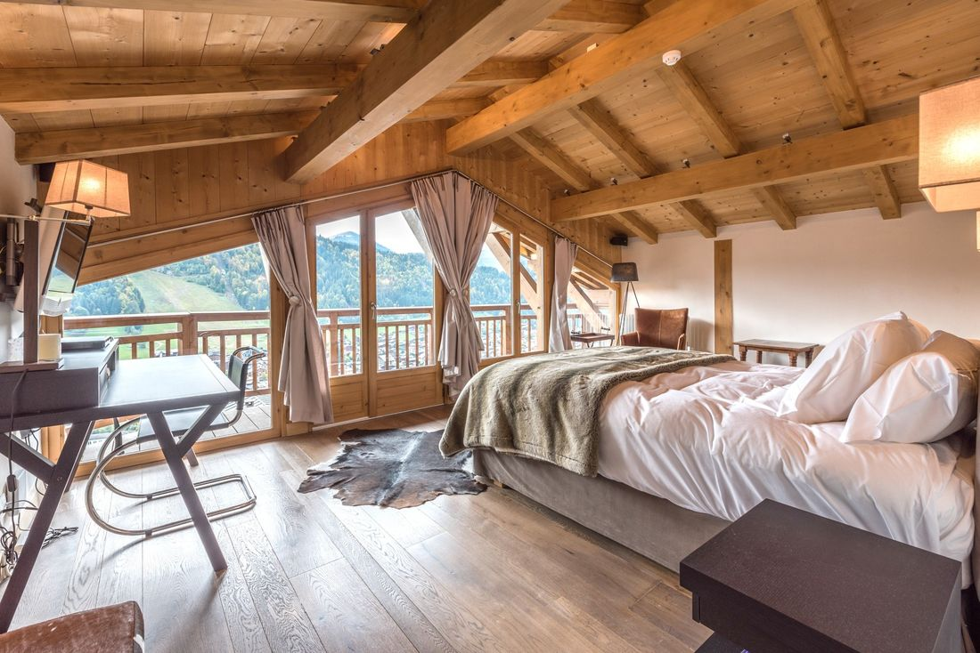Wooden double bedroom with large windows and view over the mountains at Omaroo I luxury chalet in Morzine